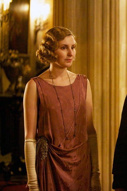 Downton Abbey's Lady Edith wears a 1920s flapper-influenced evening gown with a dropped waist and long necklace. ©Carnival Films / Masterpiece