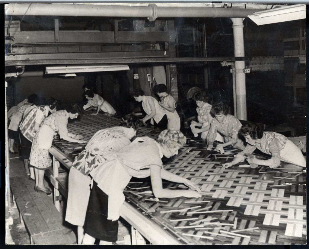 Factory workers inlaying linoleum flooring.