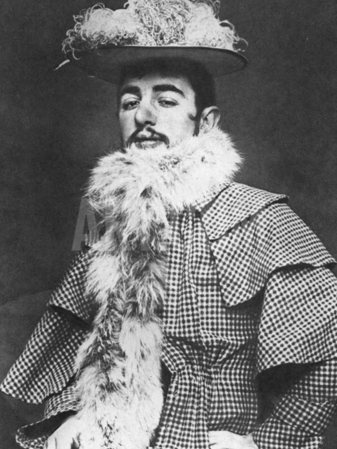 Henri de Toulouse-Lautrec wearing the feathered hat and boa of Jane Avril (daughter of a courtesan, Moulin Rouge dancer, and close friend), ca. 1892.